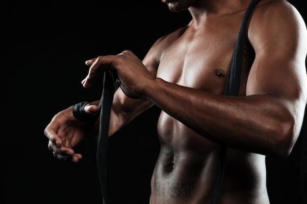 Foto recortada de jovem boxeador afro-americano de mãos, ventos bandagens de boxe