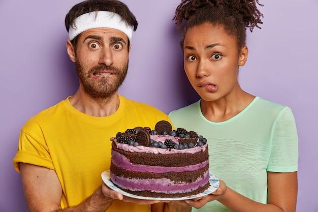 Foto recortada de jovem casal diversificado mordendo os lábios