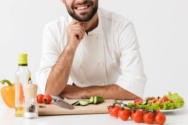 Foto recortada de jovem chef satisfeito em uniforme cozinhando com legumes frescos.