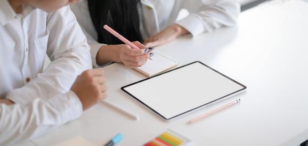 Foto recortada de jovem designer trabalhador trabalhando em seus conceitos, juntamente com tablet mock-up