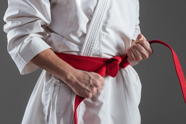 Foto recortada de jovem desportista vestido de quimono praticando caratê enquanto aperta a faixa vermelha isolada sobre fundo cinza.