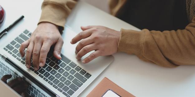 Foto recortada de jovem digitando no computador portátil enquanto trabalhava em seu projeto