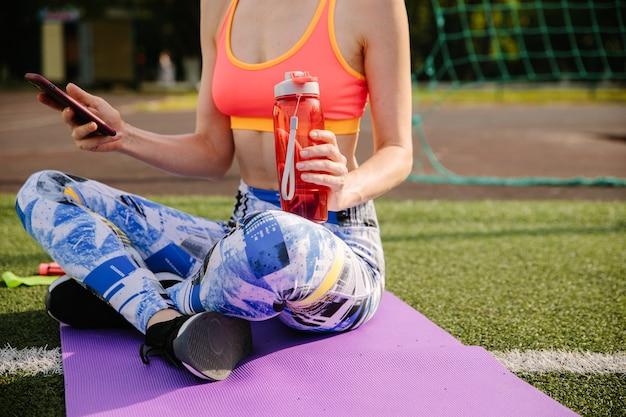 Foto recortada de jovem em roupas esportivas, senta-se no tapete, bebe água e usa um smartphone.
