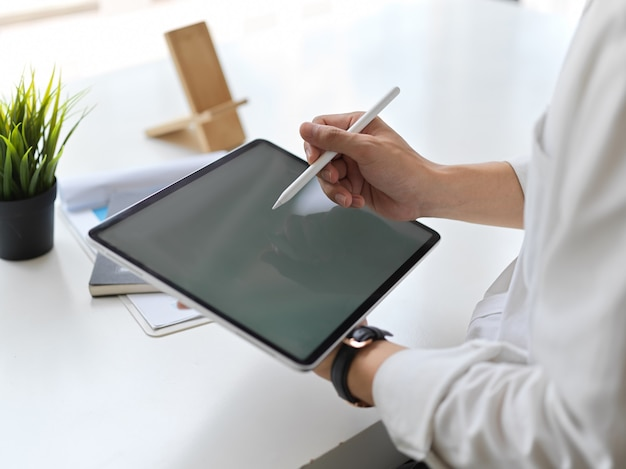 Foto recortada de jovem empresário escrevendo sobre simulação de tablet em um escritório moderno