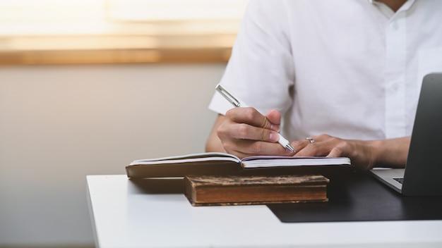 Foto recortada de jovem escrevendo informações no caderno.