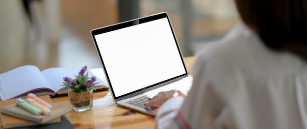 Foto recortada de jovem estudante digitando no laptop de tela em branco com notebook e artigos de papelaria