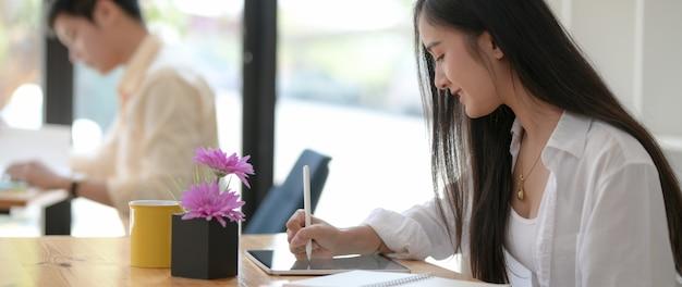 Foto recortada de jovem estudante feminino, escrevendo sobre tablet com caneta stylus