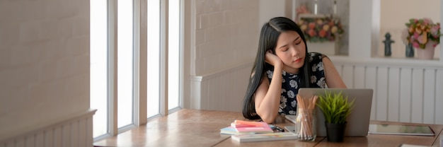 Foto recortada de jovem estudante universitária sentindo-se tentada ao fazer a lição