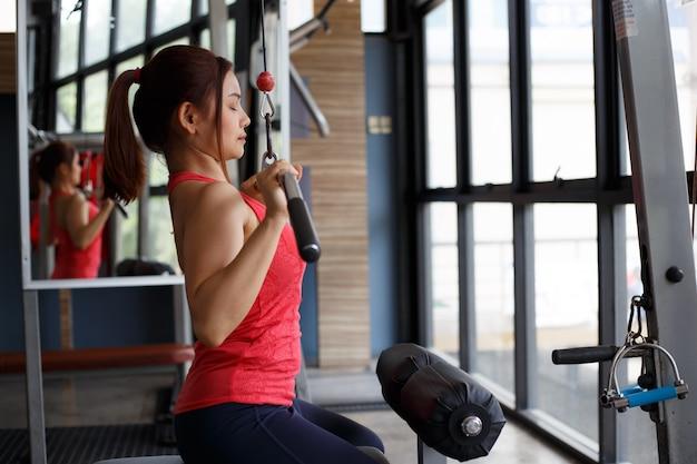 Foto recortada de jovem forte, puxando o equipamento de treino no ginásio.
