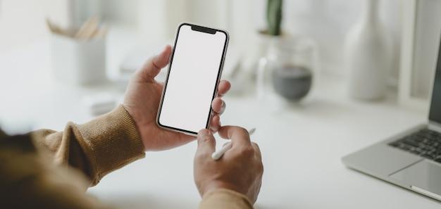 Foto recortada de jovem freelancer masculino segurando o smartphone de tela em branco