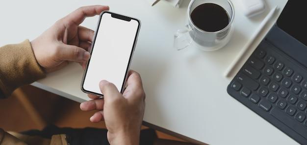 Foto recortada de jovem segurando o smartphone de tela em branco