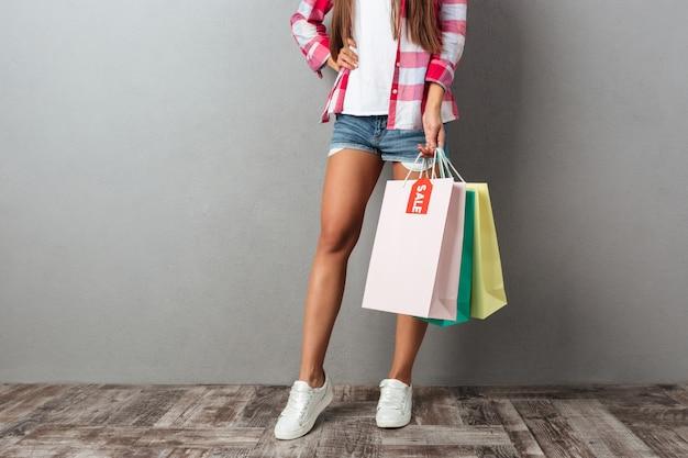 Foto recortada de jovem segurando sacolas de compras