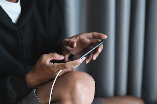 Foto recortada de jovem sentado no chão da sala de estar e usando o celular para jogar.