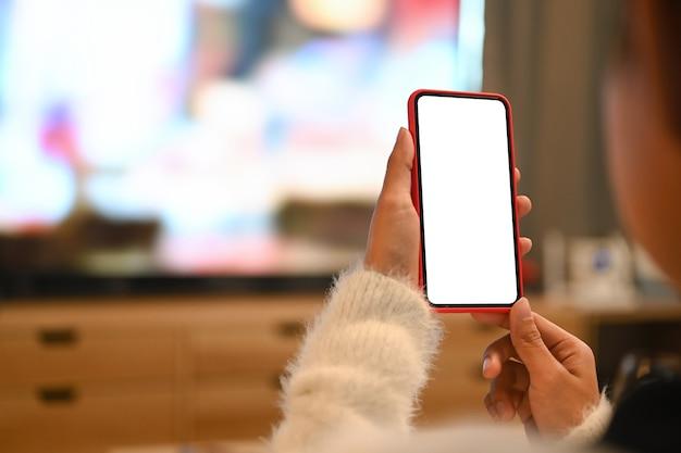 Foto recortada de jovem usando telefone celular de tela em branco enquanto está sentado na sala de estar.