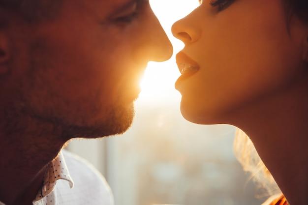 Foto recortada de jovens amantes se beijando perto da janela em casa