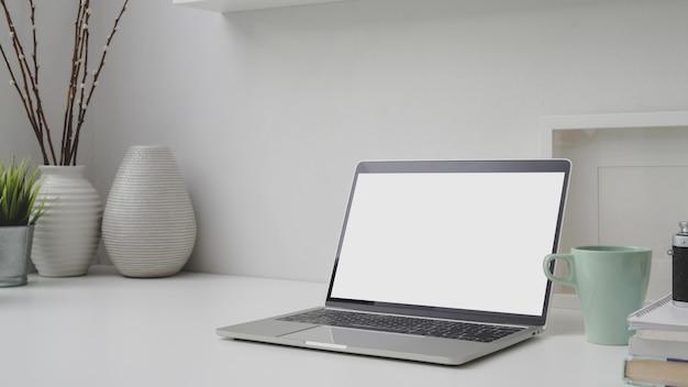 Foto recortada de local de trabalho com laptop de tela em branco, molduras, decorações e espaço de cópia