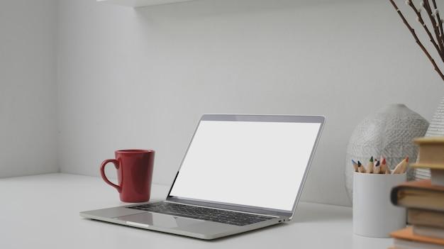Foto recortada de local de trabalho com laptop, livros, xícara de café e decorações