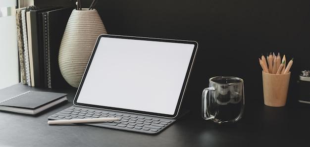 Foto recortada de local de trabalho moderno com tablet de tela em branco com material de escritório com parede preta