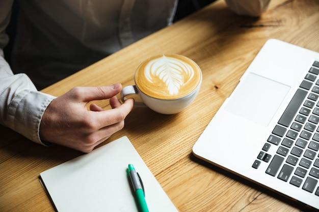 Foto recortada de mans mão na camisa branca, segurando a xícara de café