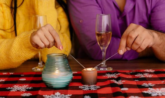 Foto recortada de mãos de casal ateando fogo a fogos de artifício sentado à mesa com taças de champanhe