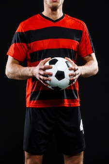 Foto recortada de mãos de goleiro com futebol