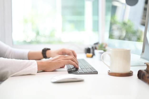 Foto recortada de mãos de jovem homem digitando no teclado em seu espaço de trabalho moderno.