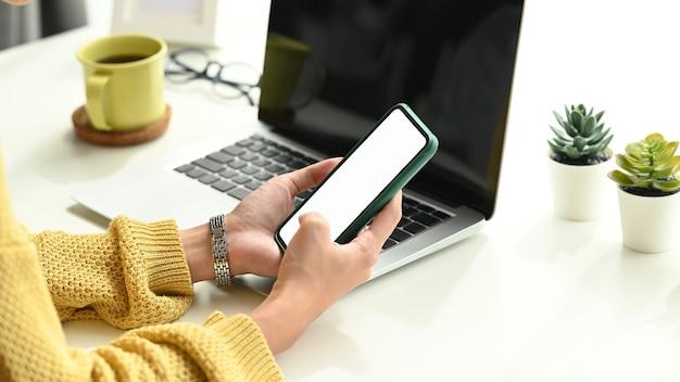 Foto recortada de mãos de mulher jovem ocupadas usando telefone celular com tela vazia na mesa de trabalho.