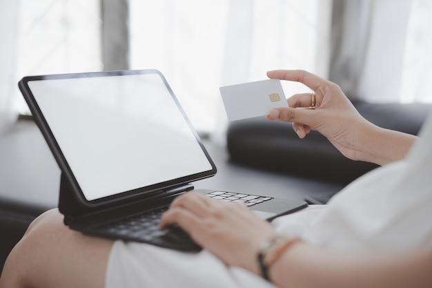 Foto recortada de mãos de mulher usando computador de tela branca do tablet, compras online com maquete de cartão de crédito em casa.