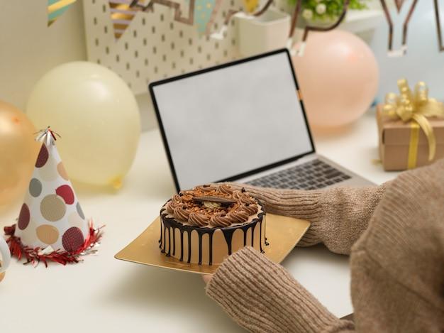 Foto recortada de mãos femininas segurando um bolo de aniversário na mesa com decorações de aniversário e um laptop