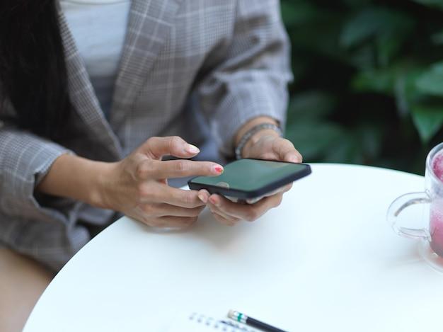 Foto recortada de mãos femininas usando smartphone na mesa de centro com bebida e notebook no café