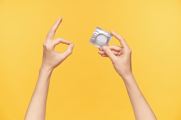 Foto recortada de mãos levantadas de uma mulher sendo levantadas enquanto posam sobre um fundo laranja com um pacote de preservativo, mostrando um gesto de ok enquanto indica que a situação está controlada