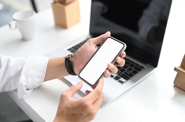 Foto recortada de mãos segurando um telefone inteligente com tela vazia na mesa de escritório branca.