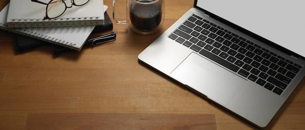 Foto recortada de mesa de trabalho com simulação de laptop, notebooks, óculos e espaço de cópia na sala de escritório