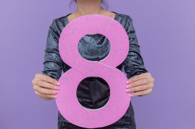 Foto recortada de mulher asiática segurando o número oito feita de papelão, comemorando o dia internacional da mulher, em pé sobre uma parede roxa