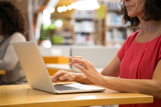 Foto recortada de mulher caucasiana, trabalhando com o laptop na biblioteca