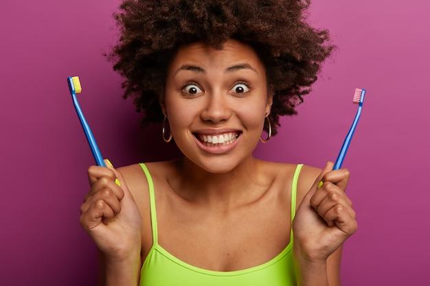 Foto recortada de mulher de cabelo encaracolado tem expressão alegre, segura duas escovas de dente, mostra dentes brancos perfeitos, tem procedimento matinal higiênico diário, pele saudável, isolada na parede roxa.