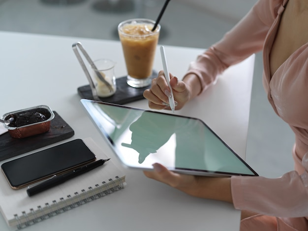 Foto recortada de mulher de negócios usando simulação de tablet de tela em branco com caneta stylus em uma confortável sala de escritório