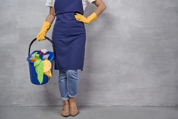 Foto recortada de mulher de uniforme e luvas de borracha amarelas segurando um balde de plástico com trapos, detergentes e diferentes produtos de limpeza em pé contra a parede cinza. serviços de limpeza, arrumação