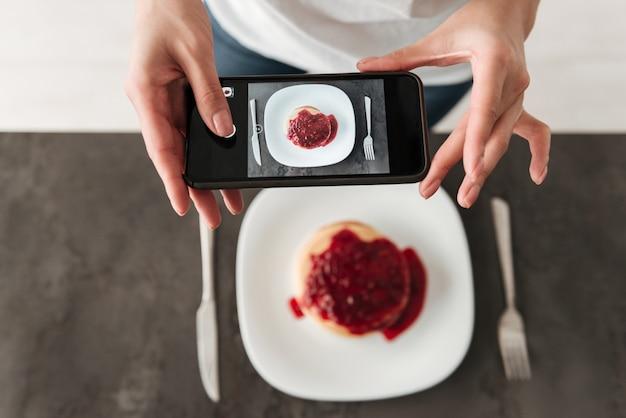 Foto recortada de mulher fazer foto de panquecas por telefone.