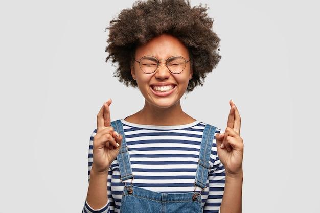 Foto recortada de mulher feliz e desejosa de pele escura cruza os dedos enquanto antecipa os resultados do exame