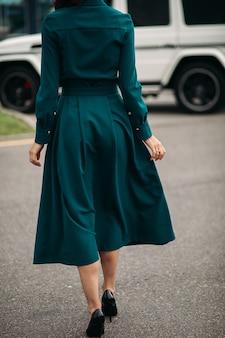 Foto recortada de mulher incógnita em vestido de esmeralda e saltos pretos andando da câmera na rua.