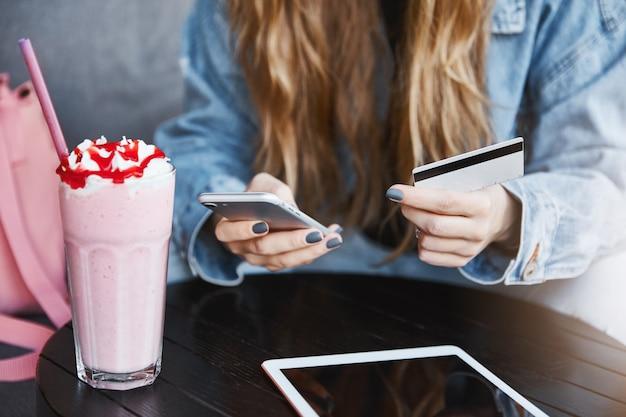 Foto recortada de mulher jovem com cabelo loiro, segurando um smartphone