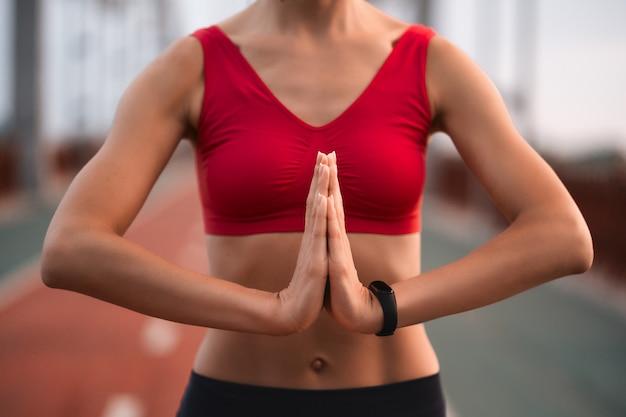 Foto recortada de mulher magra com um top esportivo vermelho em pé ao ar livre e praticando a plena consciência sozinha