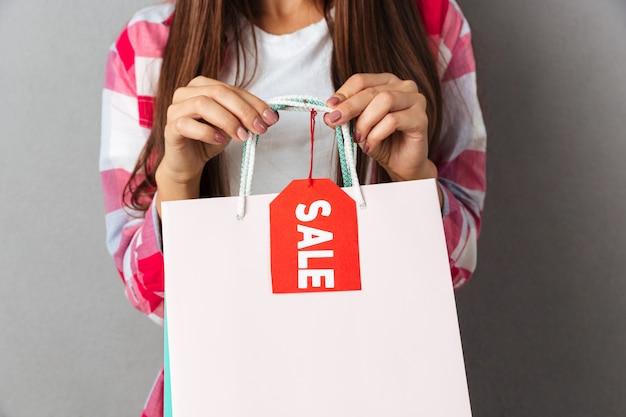 Foto recortada de mulher morena segurando sacolas de compras