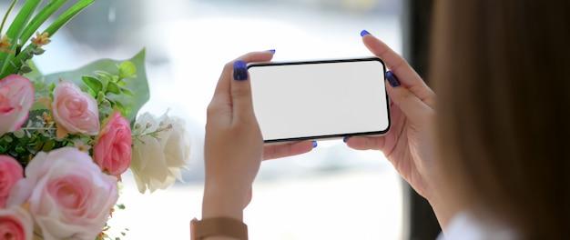 Foto recortada de mulher usando smartphone horizontal na cafeteria
