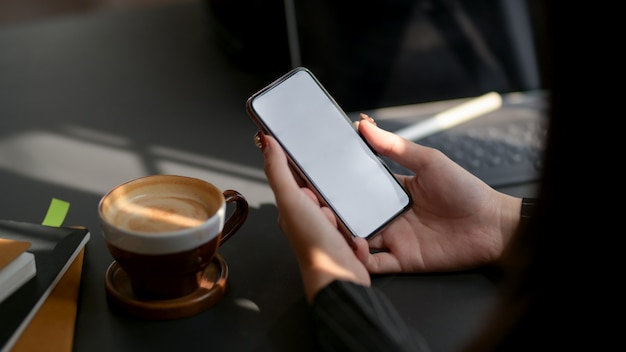 Foto recortada de mulher usando smartphone na mesa preta em local de trabalho confortável