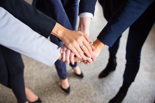 Foto recortada de mulheres juntando as mãos em círculo