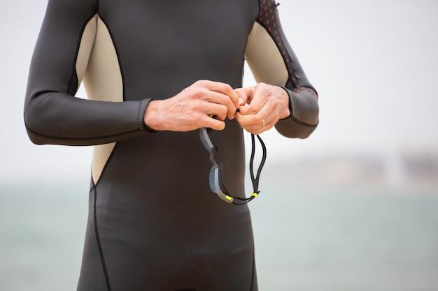 Foto recortada de nadador segurando óculos