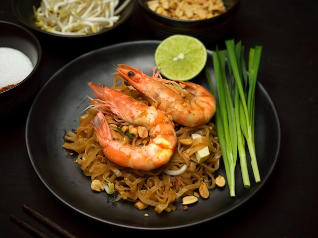 Foto recortada de pad thai, macarrão tailandês frito com camarões em um prato de cerâmica preta com limão e cebolinha