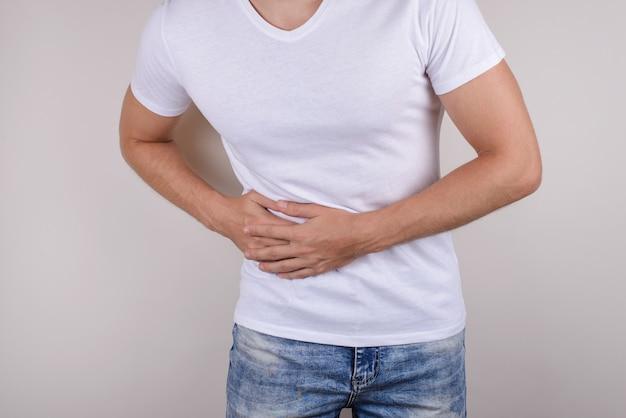 Foto recortada de perto, retrato de um cara triste triste e triste, segurando o toque do lado direito, vestindo camiseta casual, calça jeans, parede cinza isolada
